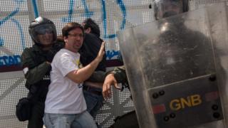 Fredy Guevara, vicepresidente de la Asamblea Nacional, se puso en el medio entre un manifestante y un funcionario de seguridad para evitar que lo detuviera.