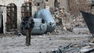 رجل يسير بين الحطام في حلب