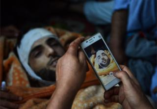 In this photograph taken on July 9, 2016, Kashmiri mourners take photographs of the body of Burhan Muzaffar Wani, the new-age poster boy for the rebel movement in the restive Himalayan state of Jammu and Kashmir, ahead of his funeral in Tral, his native town, 42kms south of Srinagar.
