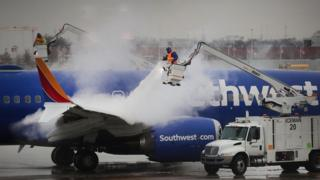 Workers de-ice a Southwest Airline's aircraft at Midway Airport