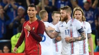 "Iceland""s midfielder Aron Gunnarsson (R) taps Portugal""s forward Cristiano Ronaldo (L) on the shoulder"