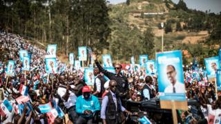 Rwandan President Paul Kagame (C) greets a crowd of supporters holding electoral posters, as he arrives for a rally in Gakenke, on 31 July 2017