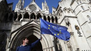 'People's Challenge' member waves an EU flag outside the Royal Courts of Justice on October 13, 2016 in London, England