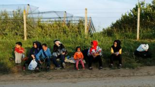 A group of migrants rest on the Serbian side of the border near Sid, 16 September 2015.
