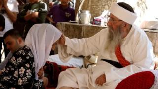 """"""" الشيخ الإيزيدي الكبير"""" يبارك امرأة في """"عيد ئيزي"""" بعد ثلاثة أيام من الصيام. أكتوبر/تشريم الأول 2017 في معبد لالش بإقليم كردستان العراق"""