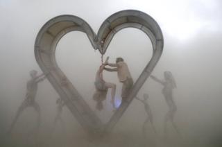 Burning Man participants perform a shibari rope scene during a driving desert dust storm inside the heart of the Identity Awareness - Family art project created by artist Shane Pitzer on the 2nd day of the annual Burning Man arts and music festival in the Black Rock Desert of Nevada, U.S. August 29, 2017