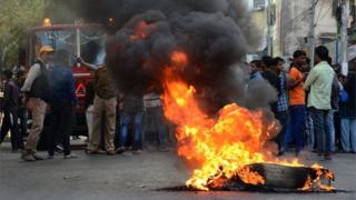 People protest by burning tyres on the street during the twelve hours Assam bandh or strike call, given by North East Student Organization (NESO) in protest against the Citizenship (Amendment) Bill (CAB