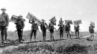 British troops taking a batch of duck-boards across marshy ground, during the Battle of the Somme
