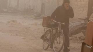 رجل يغطي وجهه من الرماد المتصاعد جراء القصف المستمر