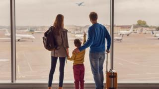 family in airport watching plane take off