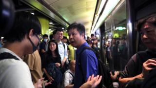 An angry stranded passenger argues with Anti-extradition bill protesters