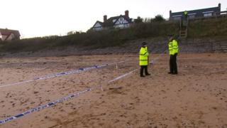 Three police officers standing by a cordon on Thorpeness beach.