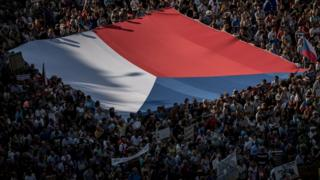 People carry a large Czech national flag as thousands of demonstrators gather to protest against Czech Prime Minister Andrej Babis on 4 June