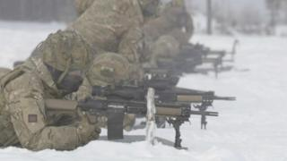 Soldiers lying down shooting rifles in the snow