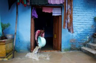 A woman tries to clear floodwaters from her home in Hunsur town in the southern state of Karnataka on 10 August 10 2019