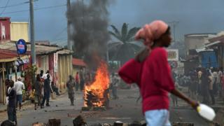 A woman walks past a burning barricade during a demonstration against in Bujumbura, Burundi -May 2015
