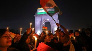 People attend a vigil in front of India Gate war memorial in Delhi, for personnel killed on Thursday