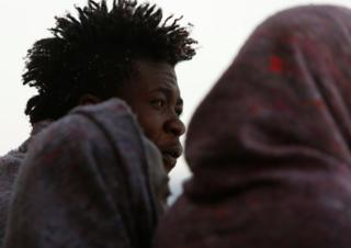 A migrant looks out towards the Maltese island of Gozo after a rescue operation off the coast of Libya