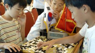 Chinese student playing the game Go against a South Korean student