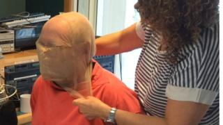 Spit hood designer Paula Romero fits the guard on BBC Sheffield presenter Rony Robinson
