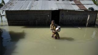 A flood affected woman wades through the water near her partially submerged house in Morigaon district, east of Gauhati, northeastern Assam state,