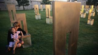 Aren Almon (in 2001) crouches with her daughter, Bella, at the memorial chair of her daughter, Baylee