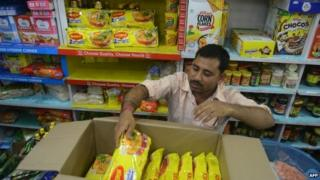 "An Indian shopkeeper removes packets of Nestle ""Maggi"" instant noodles from the shelves in his shop"