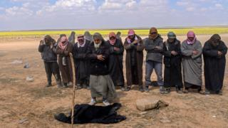 Men suspected of being Islamic State group's members pray at a screening area held by the US-backed Kurdish-led Syrian Democratic Forces (SDF), after they fled the embattled IS holdout of Baghouz in the eastern Syrian province of Deir Ezzor, on March 6, 2019