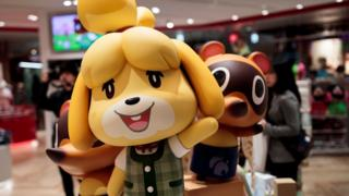 Promotional shop displays show figures of some of Animal Crossing's main characters