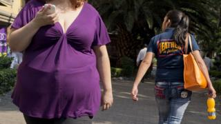An overweight Mexican woman walking down the street.