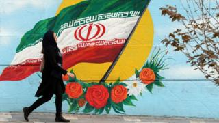 A woman walking in front of a mural featuring the Iran flag