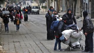 Residents of rebel-held Aleppo walk through the Qadi Askar district (30 November 2016)