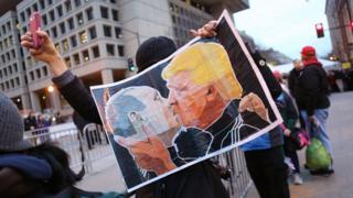 Протестувальник із плакатом з обличчями Трампа і Путіна