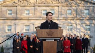 Prime Minister Justin Trudeau at a podium with his new cabinet standing behind him