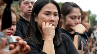 Members of the Filipino community in Cyprus attending a vigil for the victims on April 26. One holds a candle.