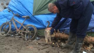 A man stroking a cat in the migrant camp