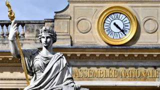 The French National Assembly is seen in this close-up photograph, framing the sign and golden clock on the facade and also the statue of a woman holding a golden sceptre which stands before the entrace