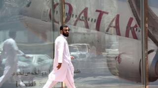 Человек на фоне эмблемы Катарских авиалиний