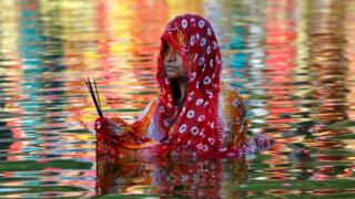 A Hindu woman stands in a lake