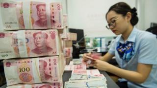 Một nhân viên ngân hàng Trung Quốc đếm các tờ tiền nhân dân tệ và đô la Mỹ tại quầy giao dịch ngân hàng ở Nam Thông, thuộc tỉnh miền đông Giang Tô của Trung Quốc vào ngày 28/ 8.