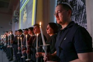 People take part in a memorial ceremony for Holocaust victims
