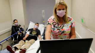 An emergency room nurse (R) treats a hospital patient for flu this month in Escondido, California