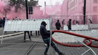 Protesters dressed in black build a barricade amid tear gas smoke during a demonstration to protest against the pension overhauls, in Nantes, on December 5, 2019,
