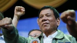 President Rodrigo Duterte raises his fist during a rally on September 13