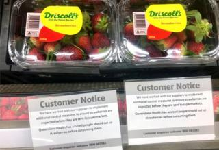 A customer notice near supermarket strawberries advises shoppers to cut them up before eating them