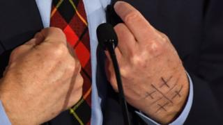 Symbol on Tom Steyer's hands