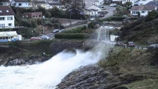 Waves crash over the road at Mumbles, Swansea Bay