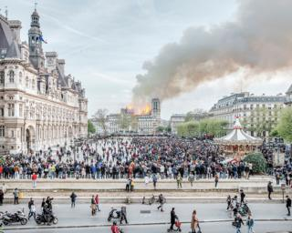 Crowds gather in Paris as the Notre Dame cathedral burns in the background