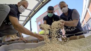 Italian police inspect tubs containing counterfeit Captagon pills