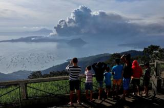 Residents look at the erupting Taal Volcano in Tagaytay City, Philippines, January 13